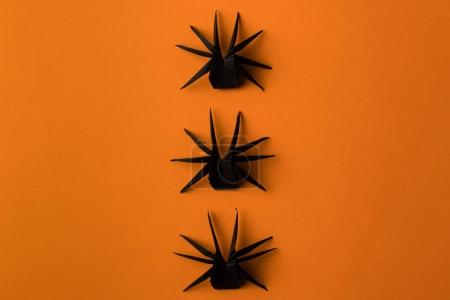 Photo for Black origami spiders for halloween, isolated on orange - Royalty Free Image