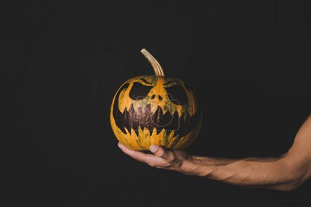 man holding pumpkin with creepy face
