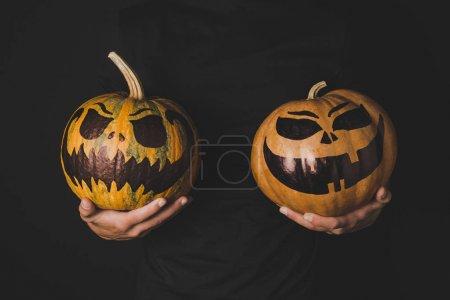 man with pumpkins in hands