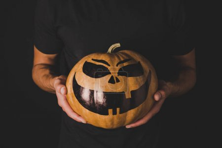 Man with pumpkin for halloween in hands