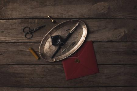 Photo for Composition of tray with ink pen and red envelope on rustic wooden table - Royalty Free Image