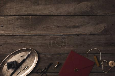 Photo for Composition of red envelope and decorative tools on dark wooden table - Royalty Free Image