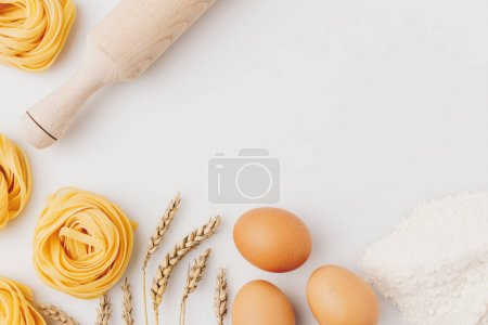 Photo for Top view of raw pasta and ingredients with rolling pin - Royalty Free Image