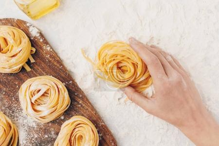 Woman holding raw pasta nest