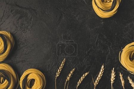 Photo pour Vue du dessus des nids de pâtes crues et du cadre de blé - image libre de droit