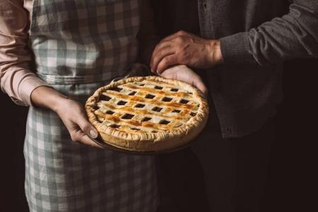 Photo for Cropped shot of woman holding homemade pie with husband near by - Royalty Free Image
