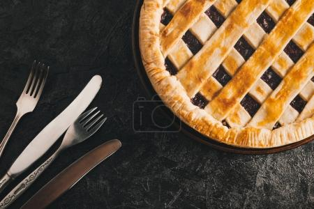 Photo for Flat lay with homemade berry pie and cutlery isolated on black table - Royalty Free Image