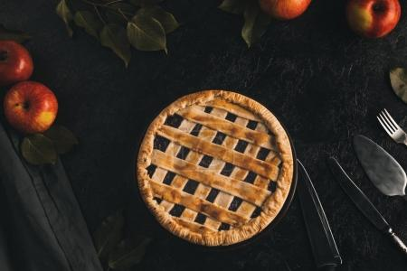 Photo for Flat lay with homemade apple pie, silverware and fresh apples isolated on black tabletop - Royalty Free Image