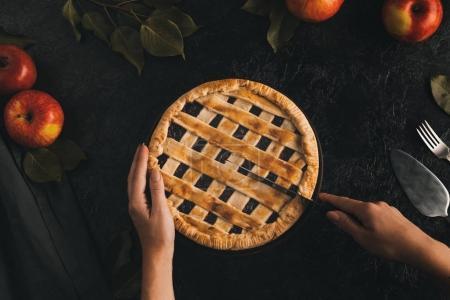 Photo pour Plan recadré de femme coupant tarte aux pommes isolée sur table noire - image libre de droit