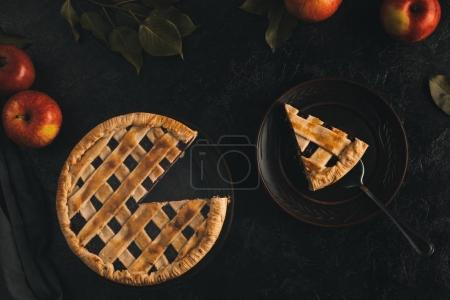 Photo for Top view of piece of apple pie on cake server on plate isolated on black surface - Royalty Free Image
