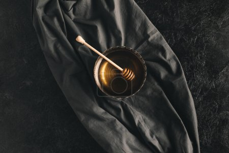Photo for Top view of honey and honey dipper in bowl isolated on black tabletop - Royalty Free Image