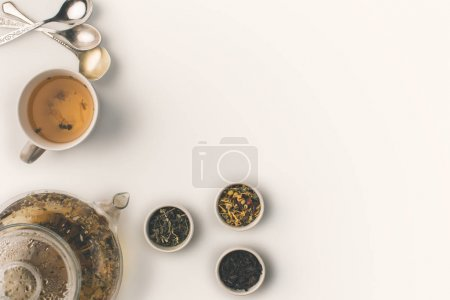 Photo for Top view of fresh herbal tea in cup and kettle, empty spoons and dry herbs in bowls on white - Royalty Free Image