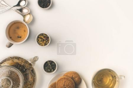Photo for Top view of fresh herbal tea in glass teapot and cups, cookies and dried herbs in bowls on white - Royalty Free Image