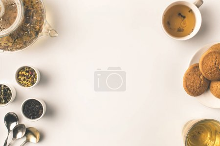 Photo for Top view of herbal tea in glass teapot and cup, cookies and dried herbs in bowls on white - Royalty Free Image