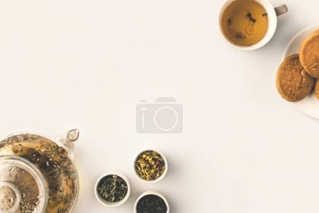 Photo for Top view of fresh organic herbal tea in kettle, dried herbs in bowls and cookies on white - Royalty Free Image