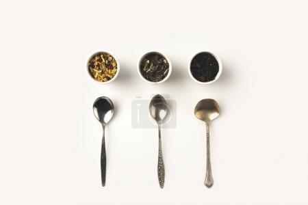 Photo pour Vue de dessus des diverses herbes séchées naturelles dans les bols et cuillères sur blanc - image libre de droit