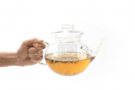 Glass teapot with herbal tea in hand