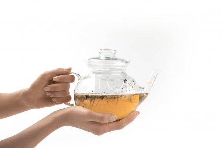 glass teapot with herbal tea in hands
