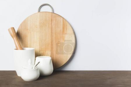 Photo pour Vue rapprochée des ustensiles de cuisine en céramique, un pilon en bois et planche à découper sur la table - image libre de droit