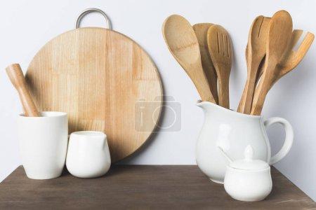 Photo pour Ustensiles de cuisine en bois, ustensiles de cuisine en céramique et planche à découper sur la table - image libre de droit