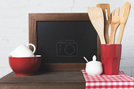 Photo for Close-up view of wooden kitchen utensils, cookware and blank board on table - Royalty Free Image