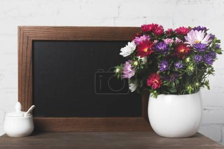 Flowers in vase and blank board