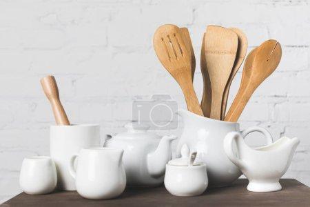 Photo pour Ustensiles de cuisine en bois et des ustensiles de cuisine en céramique sur table - image libre de droit