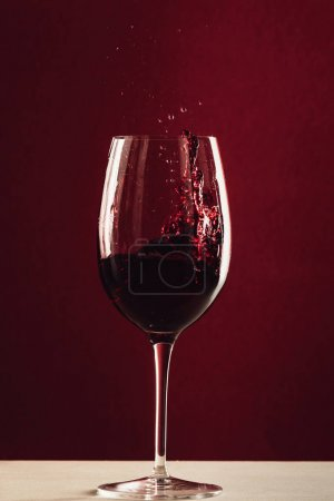 Photo for Splash of red wine in wineglass standing on tabletop on red - Royalty Free Image