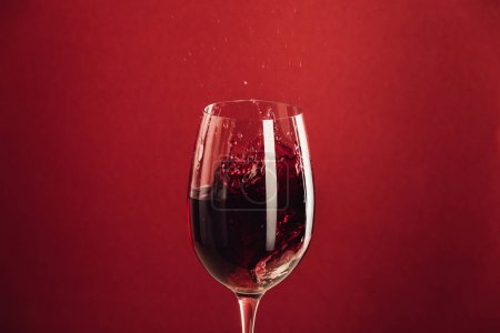 Photo for Splash of red wine in glass isolated on red with copy space - Royalty Free Image