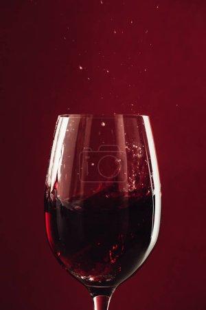Photo pour Gros plan de la tache de vin rouge en verre isolé sur rouge - image libre de droit
