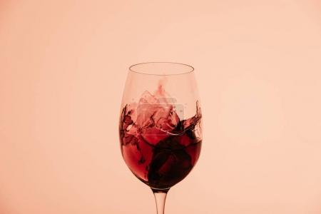 Photo for Splash of red wine in glass isolated on beige with copy space - Royalty Free Image