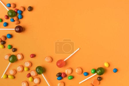 Photo for Close-up view of tasty assorted colorful halloween candies on orange - Royalty Free Image