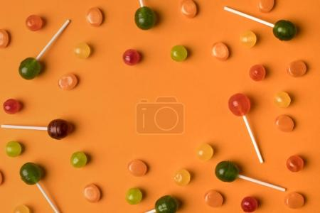Photo for Top view of assorted festive colorful candies on orange - Royalty Free Image