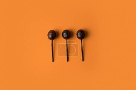 Photo for Top view of traditional black halloween lollipops on orange - Royalty Free Image