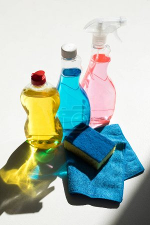 Photo for Close-up view of plastic bottles with colorful cleaning products, sponge and rag on white - Royalty Free Image
