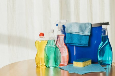 Photo for Plastic bottles with cleaning fluids, sponge, rags and bucket indoors - Royalty Free Image