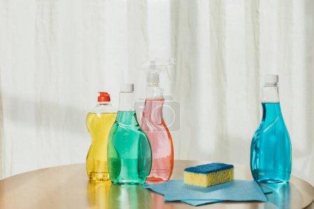 Photo pour Bouteilles en plastique avec des produits de nettoyage colorés, éponge et chiffons sur table - image libre de droit