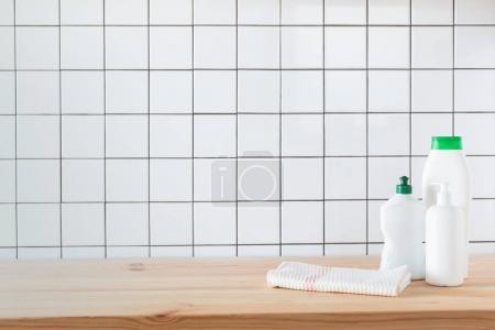Photo pour Bouteilles en plastique avec une serviette sur la table et produits de nettoyage - image libre de droit