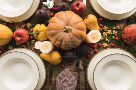 Photo for Top view of cutlery, candles and autumn decor on served table - Royalty Free Image