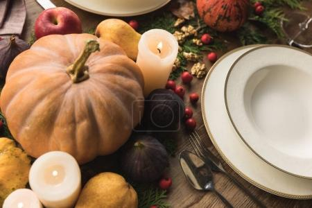 Photo for Close-up view of cutlery, pumpkins, candles and fruits on table - Royalty Free Image