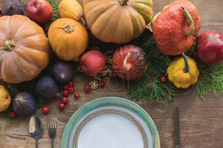 Photo for Top view of ripe autumn fruits, pumpkins and empty plate on table - Royalty Free Image