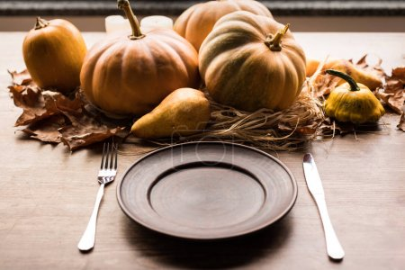 Pumpkins and cutlery on table