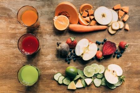 Photo pour Vue de dessus de différents smoothies dans des verres et des fruits frais avec des légumes sur la table - image libre de droit