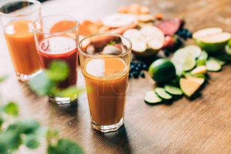 Photo pour Vue rapprochée des smoothies frais et sains aux fruits et légumes dans les verres sur la table - image libre de droit