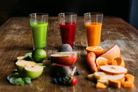 Photo pour Vue rapprochée de différents smoothies de fruits et légumes biologiques avec des ingrédients frais sur la table - image libre de droit