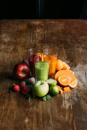 Photo for High angle view of various smoothies in glasses and fresh fruits with vegetables on wooden table - Royalty Free Image