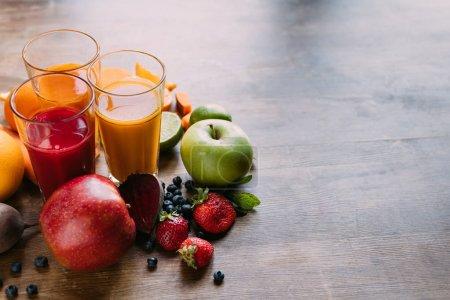 Photo pour Vue rapprochée de différents smoothies dans des verres et fruits frais avec légumes sur la table - image libre de droit