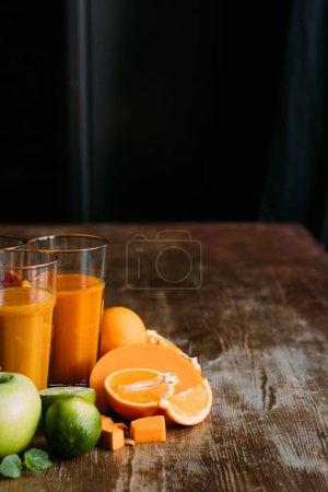 Photo pour Vue rapprochée du smoothie orange sain dans les verres et les ingrédients frais sur la table - image libre de droit