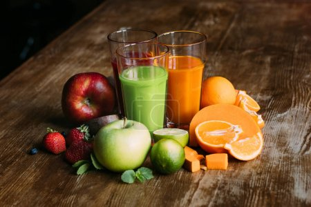 Photo for Close-up view of various smoothies in glasses and fresh fruits on wooden table - Royalty Free Image