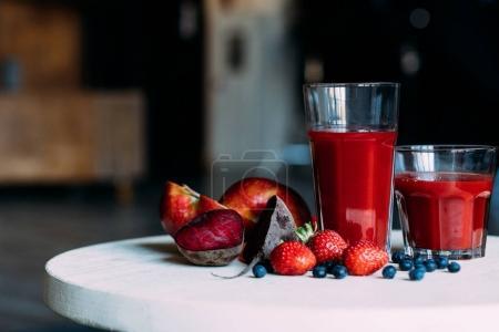 Photo pour Vue du dessus du smoothie rouge dans les verres et les ingrédients frais sur la table - image libre de droit